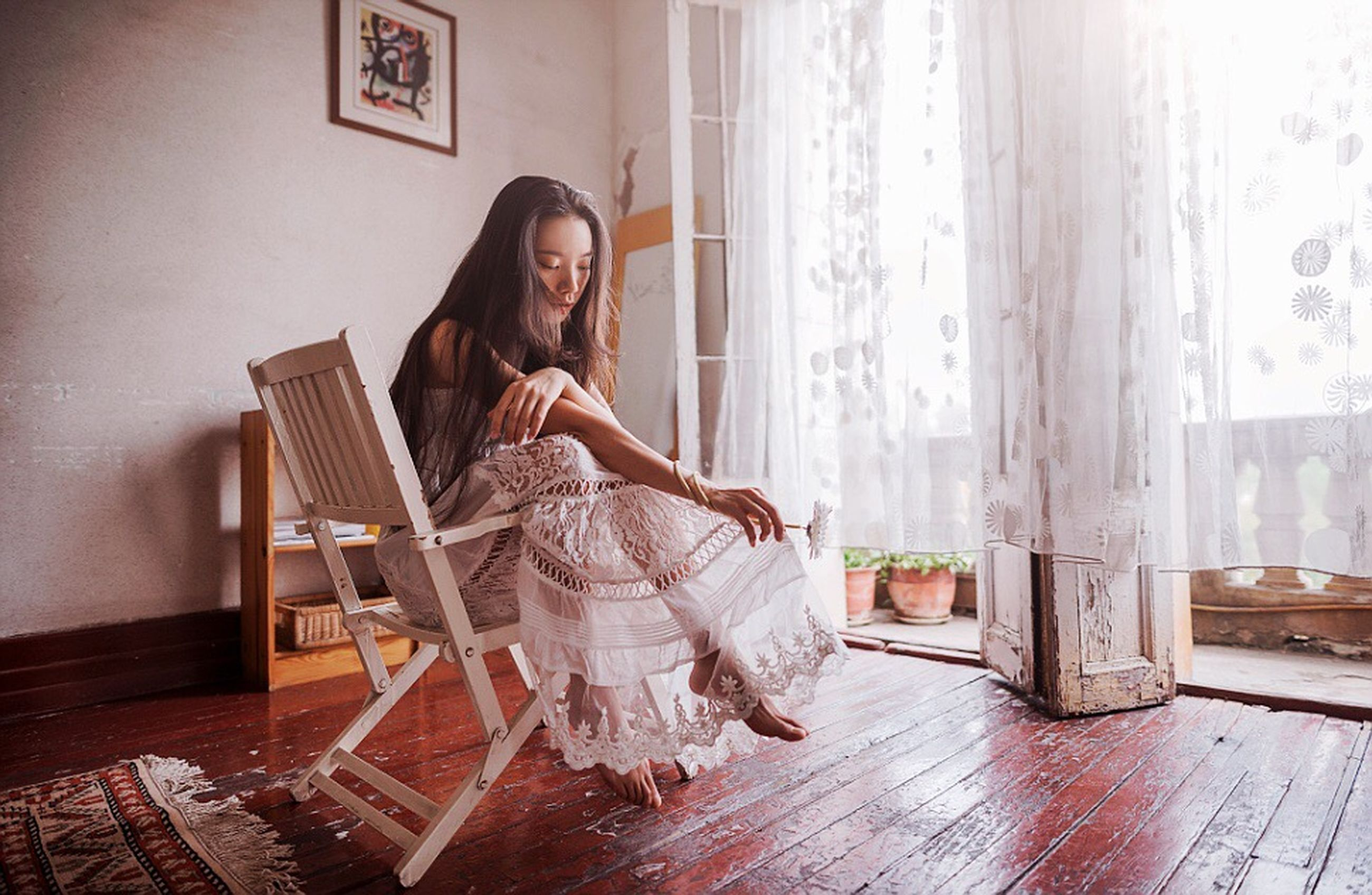 full length, sitting, young adult, young women, lifestyles, indoors, casual clothing, chair, leisure activity, long hair, person, traditional clothing, home interior, flooring, looking at camera, headscarf, in front of, front view, hands clasped, well-dressed, day