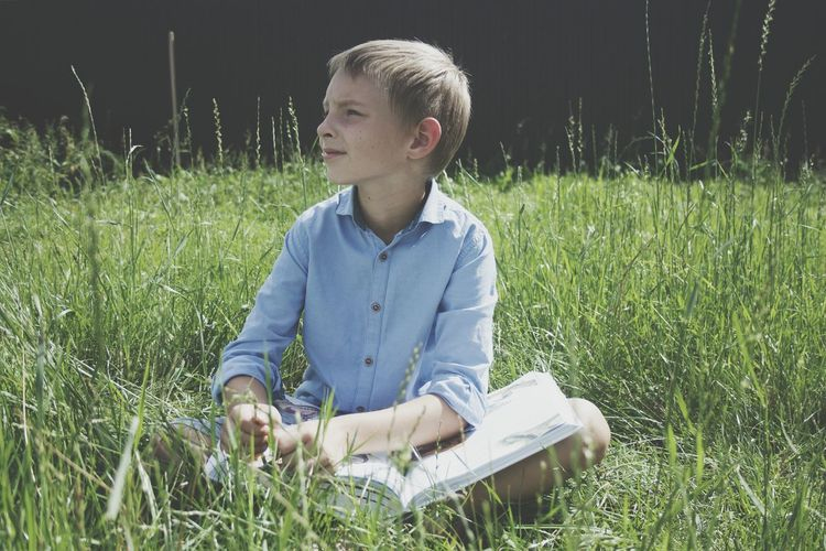 Boy with book sitting on field