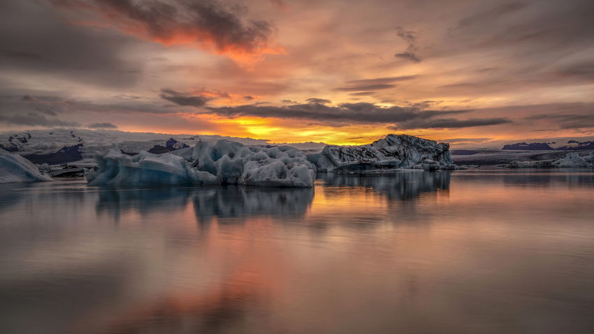 Jökulsárlón is a glacial lagoon, bordering Vatnajökull National Park in southeastern Iceland. Its still, blue waters are dotted with icebergs from the surrounding Breiðamerkurjökull Glacier, part of larger Vatnajökull Glacier. The Glacier Lagoon flows through a short waterway into the Atlantic Ocean, leaving chunks of ice on a black sand beach. Water Sky Cloud - Sky Sunset Tranquility Scenics - Nature Tranquil Scene Beauty In Nature Environment Ice Glacier Cold Temperature No People Reflection Landscape Idyllic Sea Nature Orange Color Iceberg Lagoon Global Warming Floating On Water Touriam Dusk