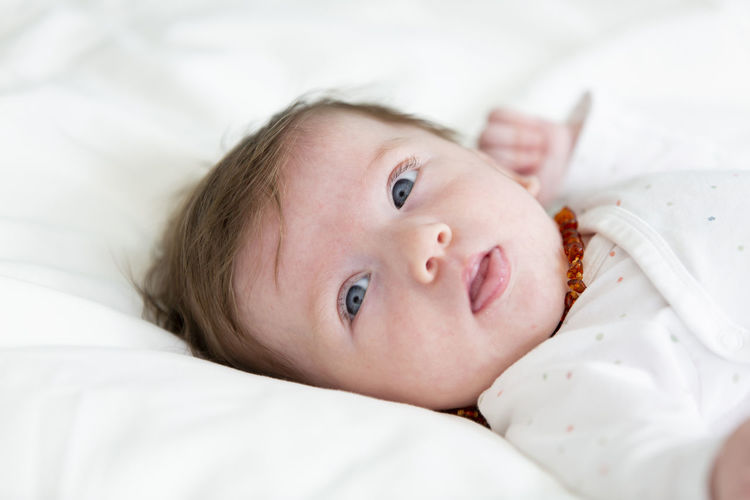 3 month old beautiful, cute baby with amber necklace Amber Baby Medicine Baby Babyhood Bed Child Childhood Cute Furniture Headshot Homeopathy Indoors  Innocence Looking At Camera Lying Down Lying On Back Necklace One Person Portrait Real People Relaxation Superstition  Young