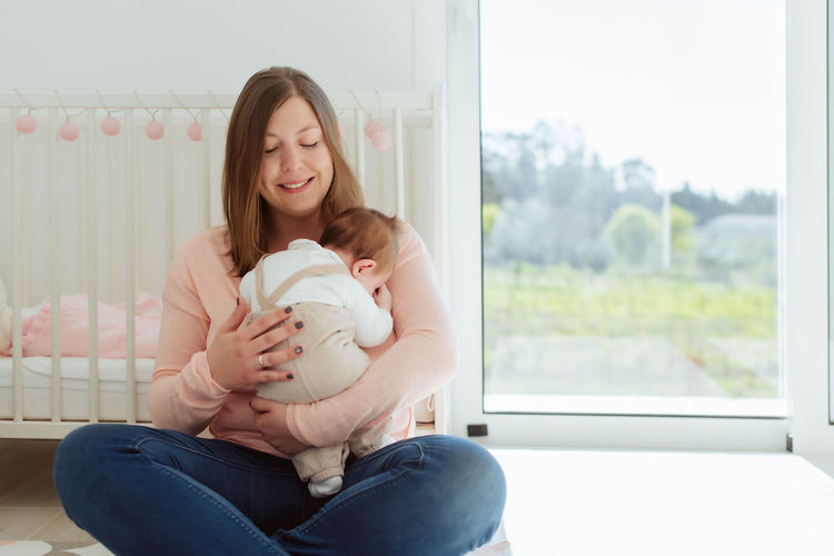 Portrait of woman holding baby while sitting at home