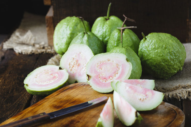 Guavas with cutting board on table