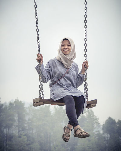 Portrait of smiling girl swinging against sky at playground