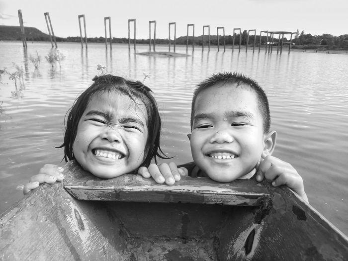 Cute sibling enjoying at lake by boat