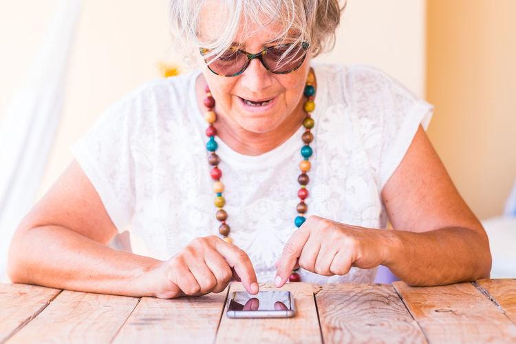 Senior woman using smart phone at table