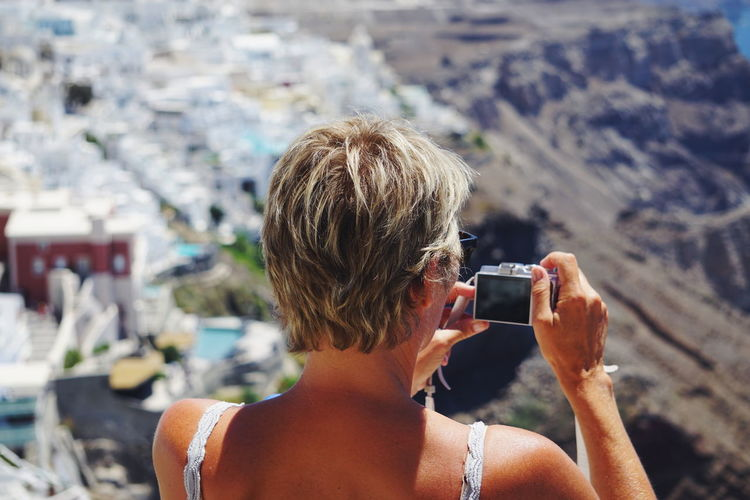 Rear view of woman photographing mountain