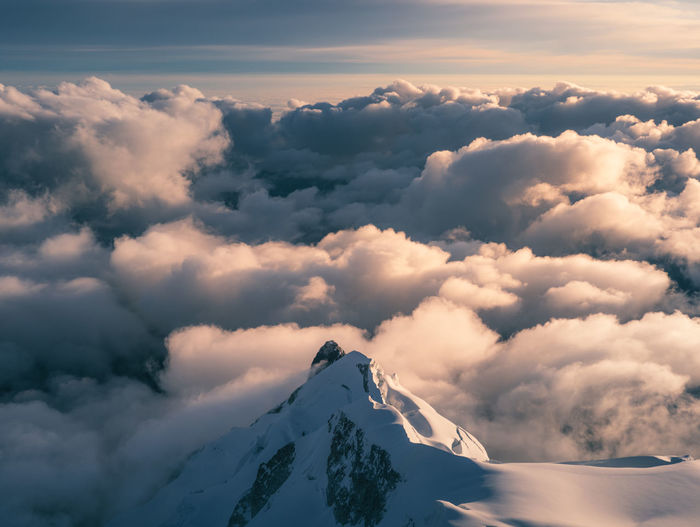 Aerial view of snowcapped mountains against cloudy sky during sunset