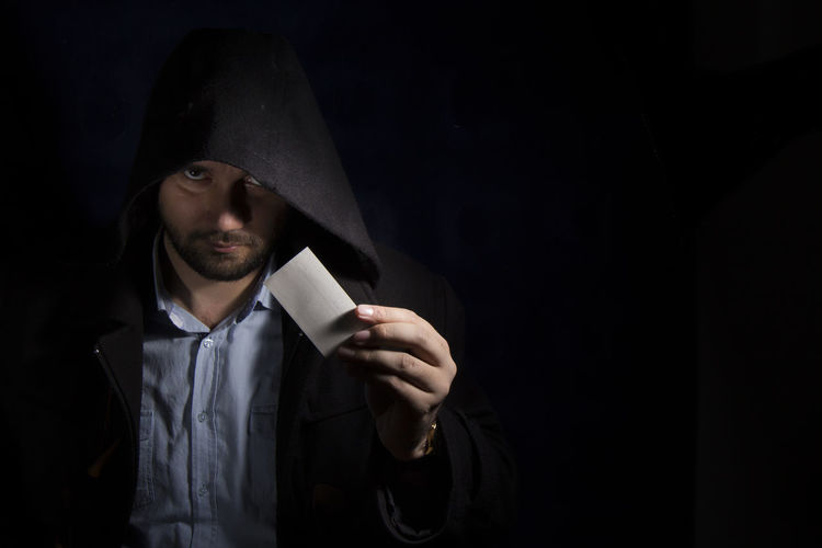 Portrait Of Serious Man Wearing Hooded Shirt While Holding Blank Business Card Against Black Background