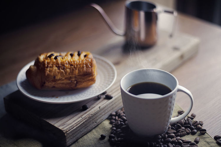 Balck coffee and croissant bread breakfast Breakfast Coffee Coffee Time Kettle Pouring Kettle Steam Wood Afternoon Tea Aroma Baked Bread Brunch Cafe Close-up Coffee - Drink Coffee Beans Coffee Break Coffee Cup Croissant Dark Background Mug Ready-to-eat Retro Styled Swan Neck Kettle Table