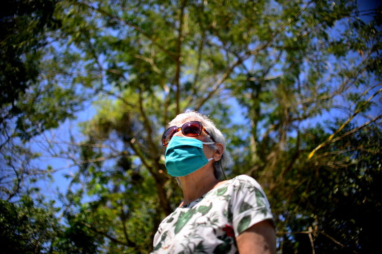 Low angle view of elderly woman wearing sunglasses and mask against trees