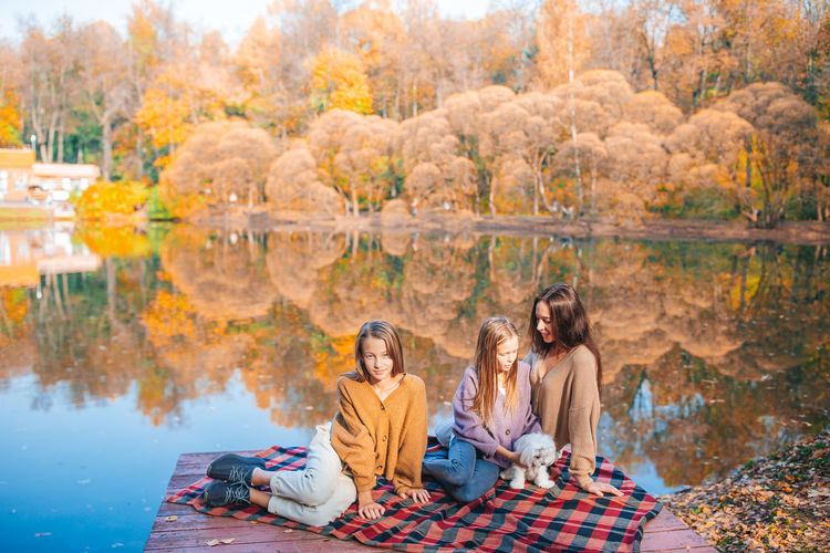 High angle view of people sitting by lake during autumn
