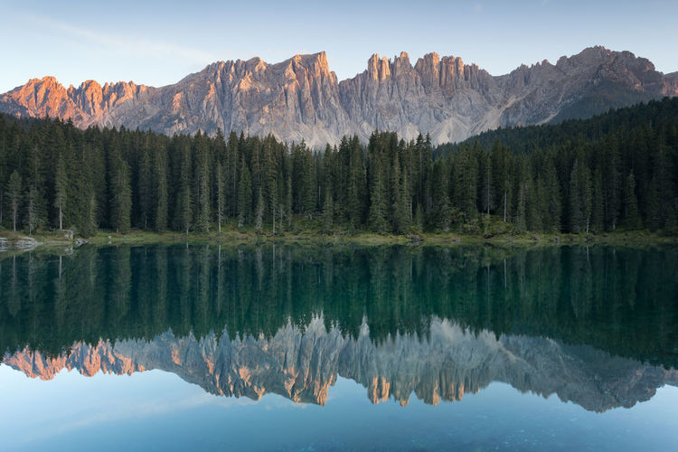 Reflection of trees in lake against mountains