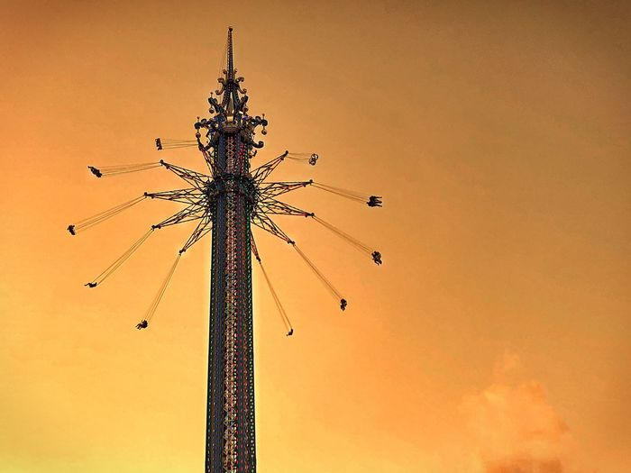 Low angle view of chain swing ride against sky during sunset