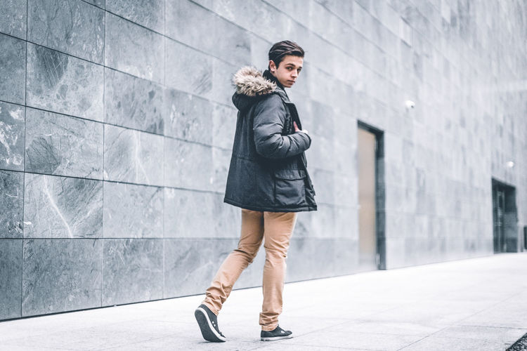 Young man walking on footpath