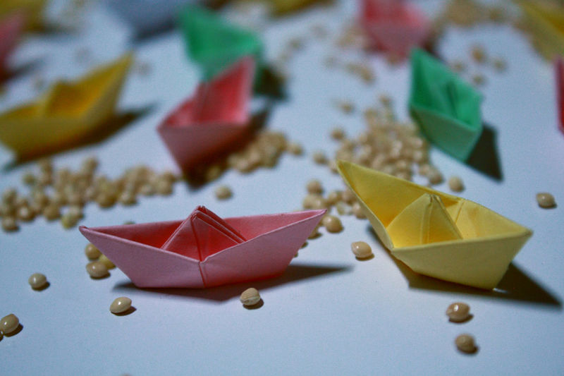 High angle view of colorful paper boats with beans on table