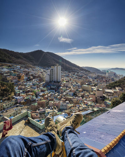 Low section of man sitting against cityscape during sunny day