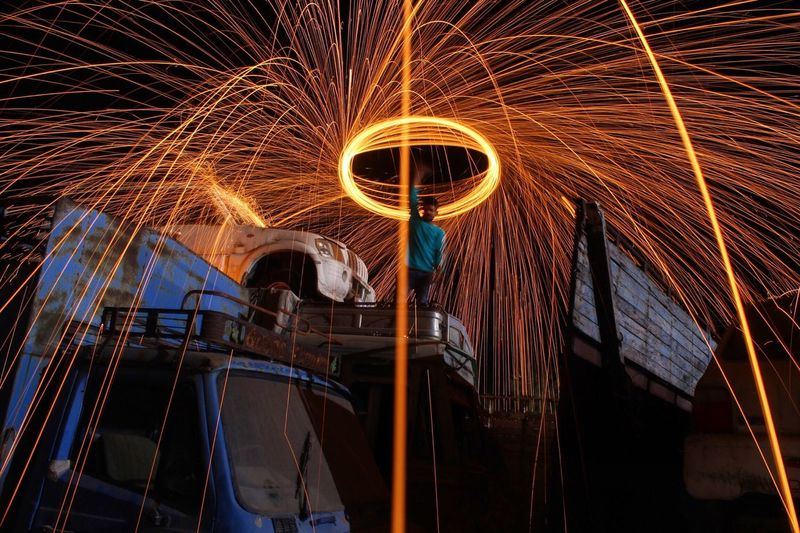 Low Angle View Of Man On Truck Spinning Wire Wool At Night