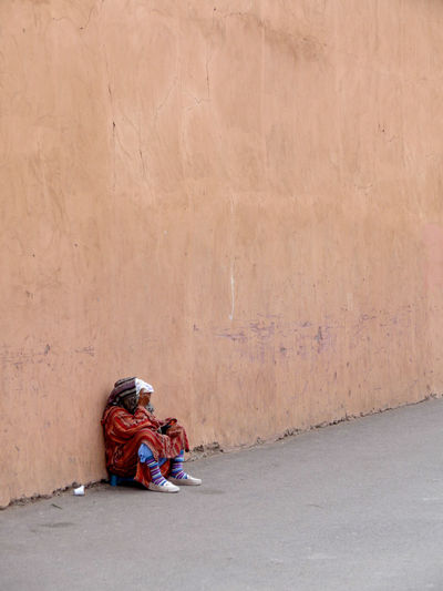Homeless Woman Sitting By Wall On Street