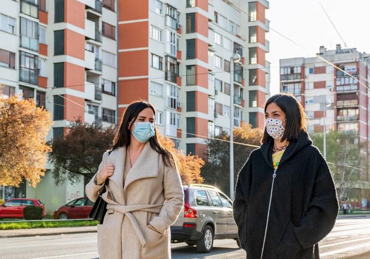 Two friends walking in city, wearing protective masks during corona virus epidemic, female, women.