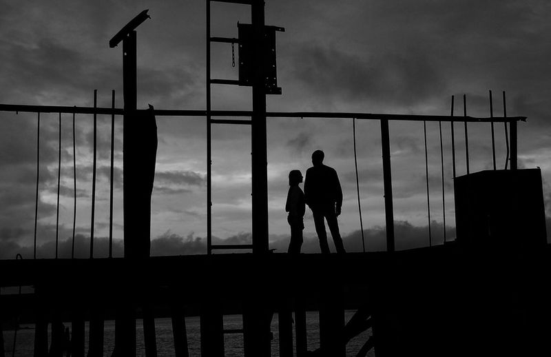 Silhouette man and girl on pier against cloudy sky