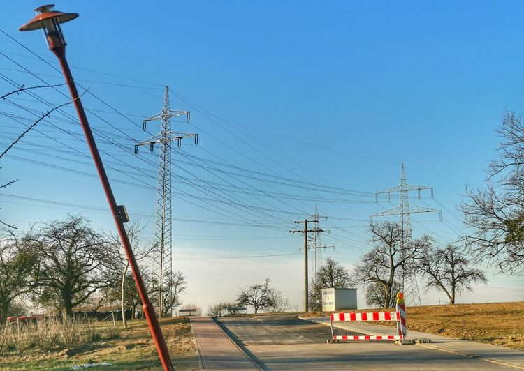 Electricity pylon by road against sky