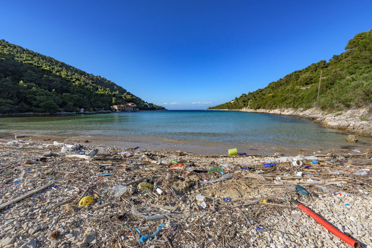 Garbage at beach against clear blue sky