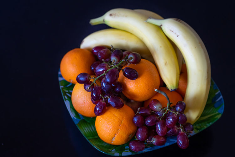 Healthy Eating Fruit Food Food And Drink Freshness Wellbeing Banana Still Life Studio Shot Indoors  Orange Color No People Orange Orange - Fruit Close-up Black Background Grape Choice Citrus Fruit High Angle View Ripe Red Currant Banana Grapes