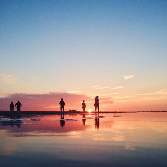 People Standing With Reflection On Wet Shore At Beach Against Sunset Sky