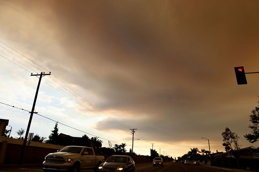 smoke from a california wildfire cover the sky in Huntington Beach California Huntington Beach CA Smoke Southern California California Wildfire Car City Cloud - Sky Motor Vehicle Nature Ominous Sky Outdoors Plant Road Sky Smoke Filled Sky Street Sunset Tree
