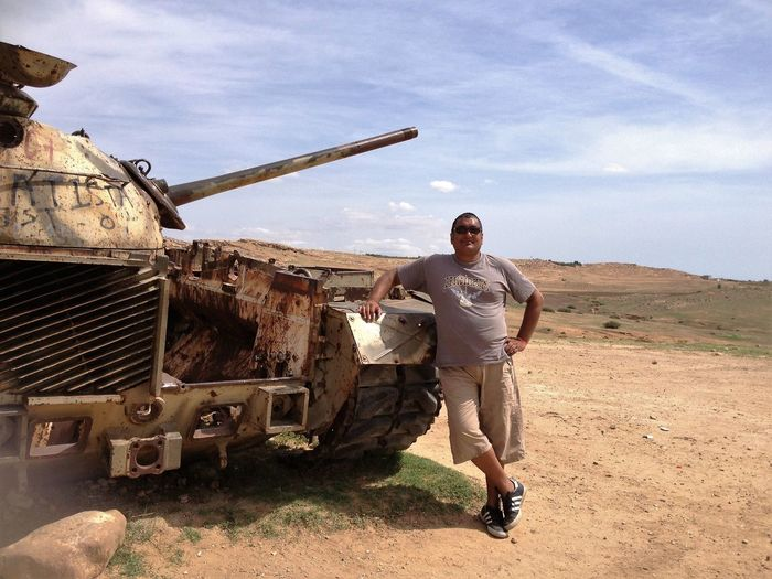 Man Standing By Abandoned Military Tank Against Sky