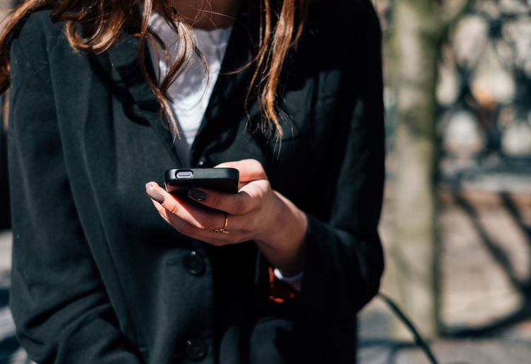 Midsection of young woman using mobile phone while standing on street