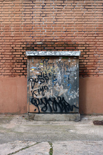 Graffiti on electric meter box against wall