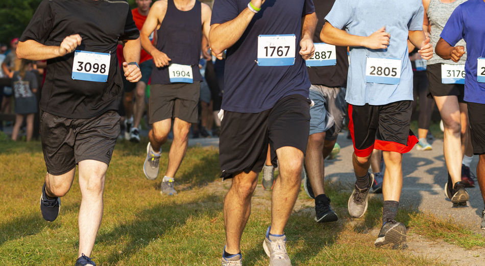 Runners running a 5k race on grass in during a very crowded event.