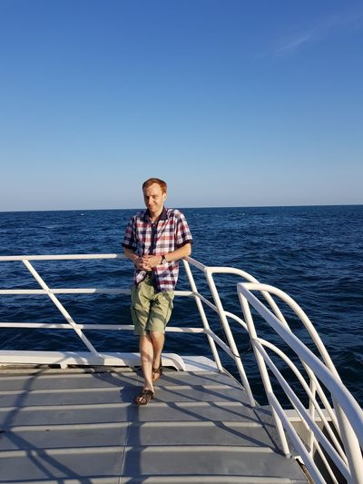 Full length of young man standing on boat deck