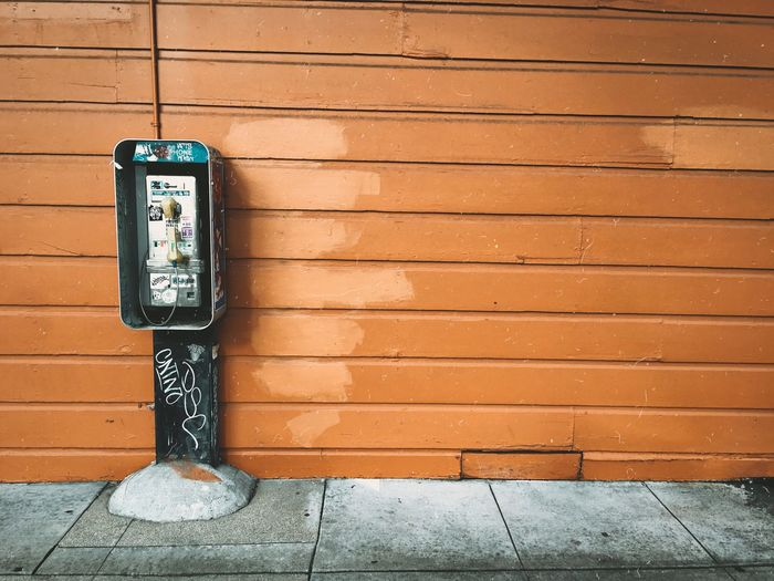 Pay phone on footpath against brown wall