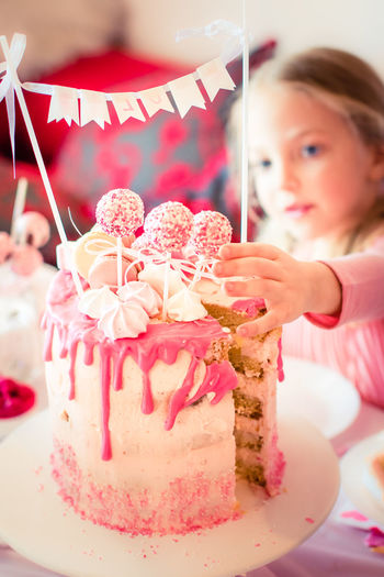 Girl Reaching For Candy On Birthday Cake At Party