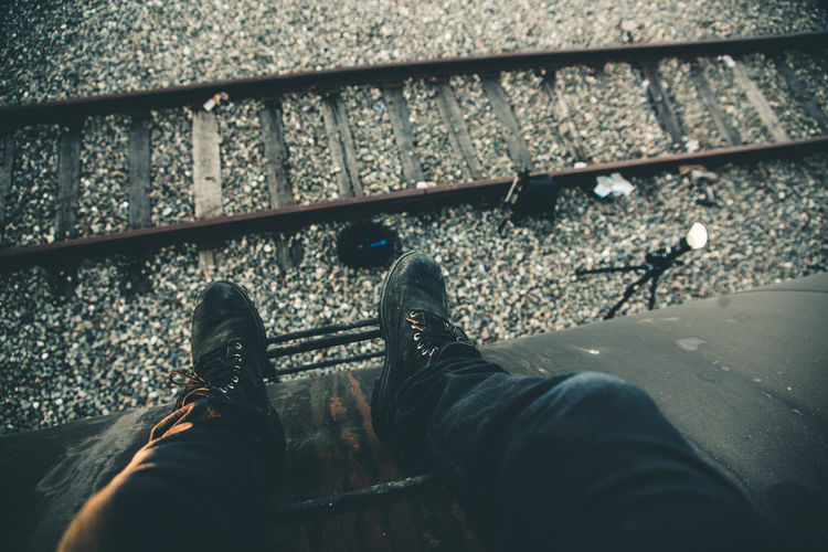 Cropped image of man sitting on cargo container by railroad track