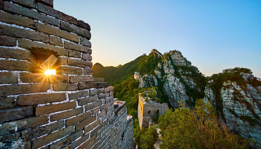 Great wall of china by mountain against sky during sunrise