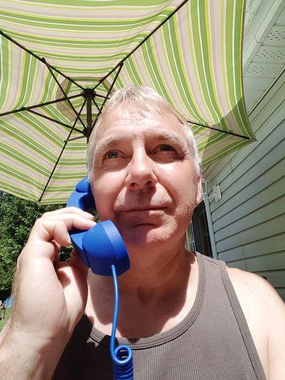 Mature man talking on landline phone while standing against parasol