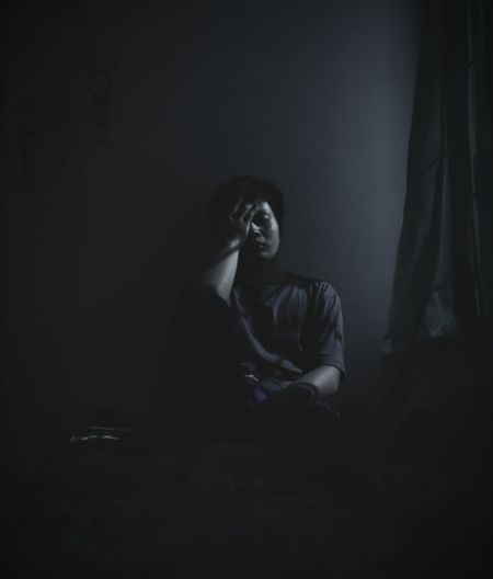Depressed Man Sitting In Darkroom