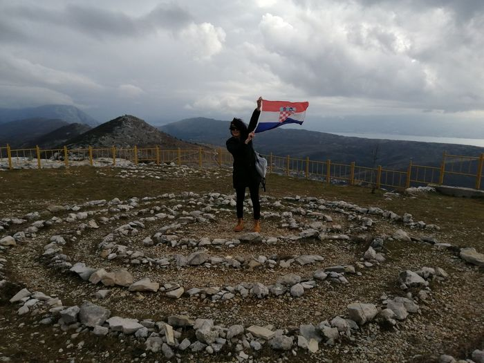 Woman waving flag while standing on mountain against cloudy sky