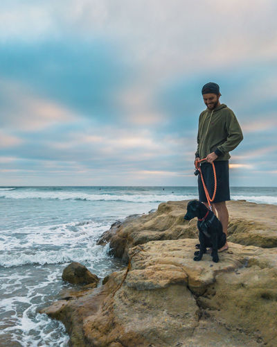 Man With Dog Standing On Rock At Beach Against Cloudy Sky