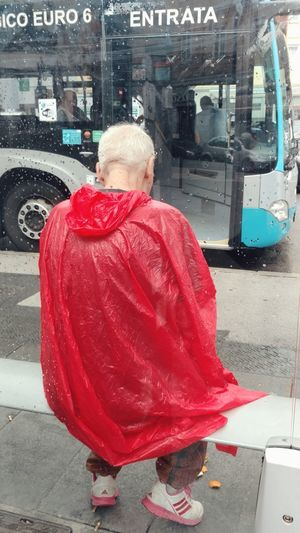 Rain in red. The Street Photographer - 2018 EyeEm Awards EyeEm Selects Italian City Bus Blond Hair Red Full Length Sitting Rear View Rainy Season Shoe Rainfall Human Leg Pair RainDrop Vehicle Rain Footwear