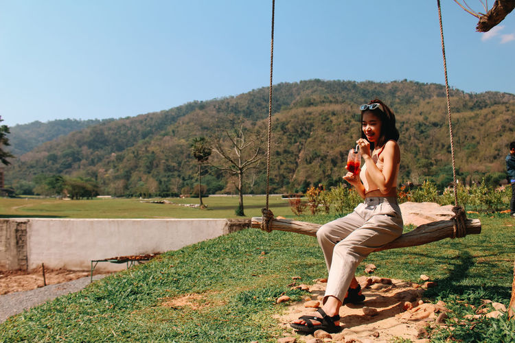 Young woman sitting on tree by mountain against sky