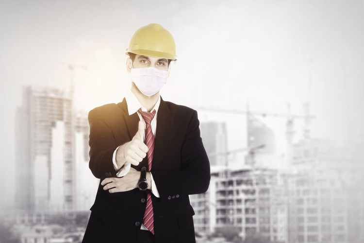 Man holding umbrella while standing at construction site