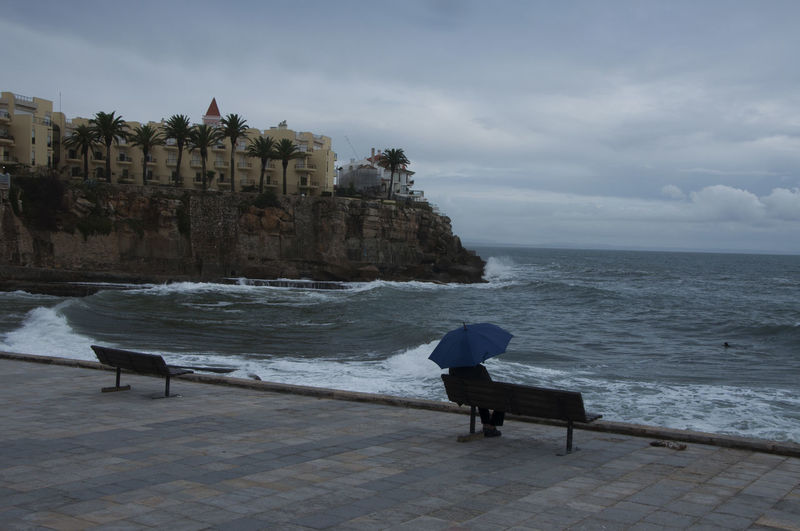 Man Carrying Umbrella Sitting In Promenade By Building Against Sea
