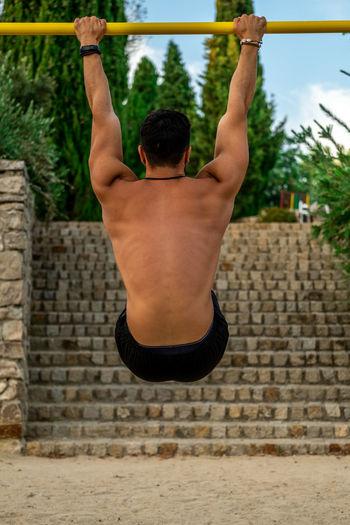 Rear view of shirtless man looking at stone wall