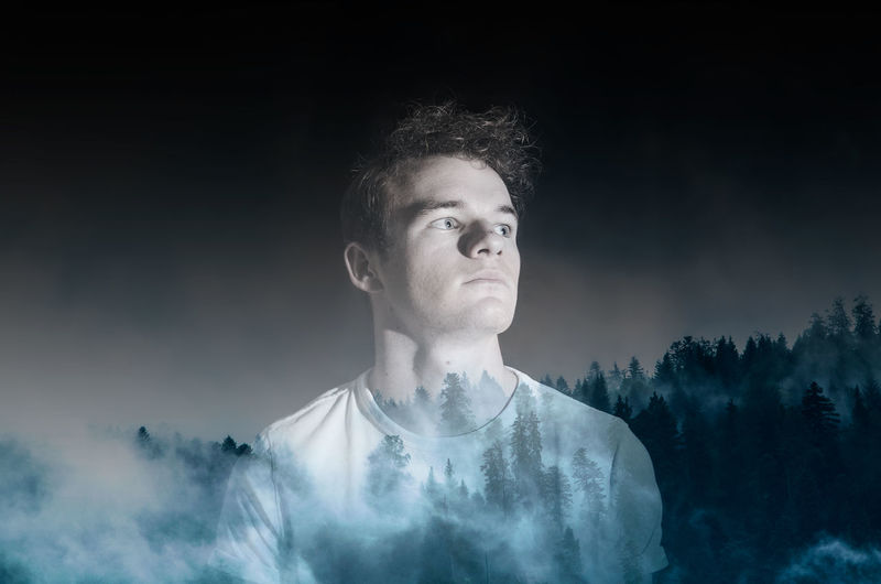 Double exposure image of young man and trees against sky at foggy night