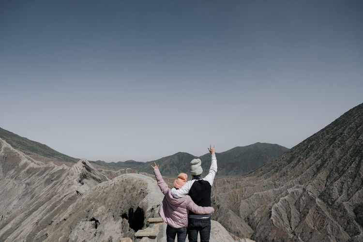 Rear View Of Couple Gesturing While Standing On Cliff At Rocky Mountain