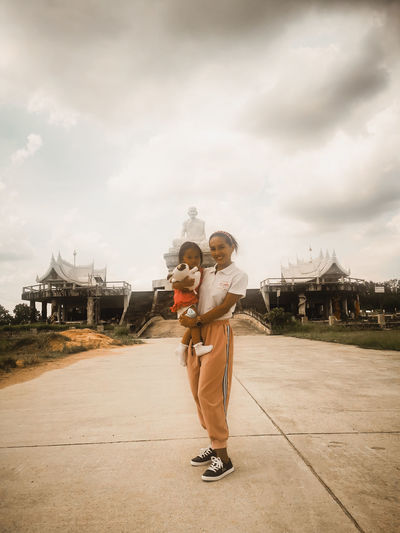 Full length of mum and daughter infront of an temple against sky